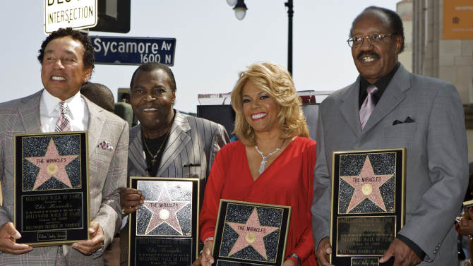 """FILE - In this March 20, 2009 file photo, members of the Motown group The Miracles, from left: William """"Smokey"""" Robinson, Warren """"Pete"""" Moore, Claudette Robinson, and Robert """"Bobby"""" Rogers, are honored with a star on the Hollywood Walk of Fame in Los Angeles. Rogers, a founding member of the group and a collaborator with Smokey, has died. Motown Museum board member Allen Rawls said Rogers died Sunday, March 3, 2013, at his home. He was 73. (AP Photo/Damian Dovarganes, file)"""