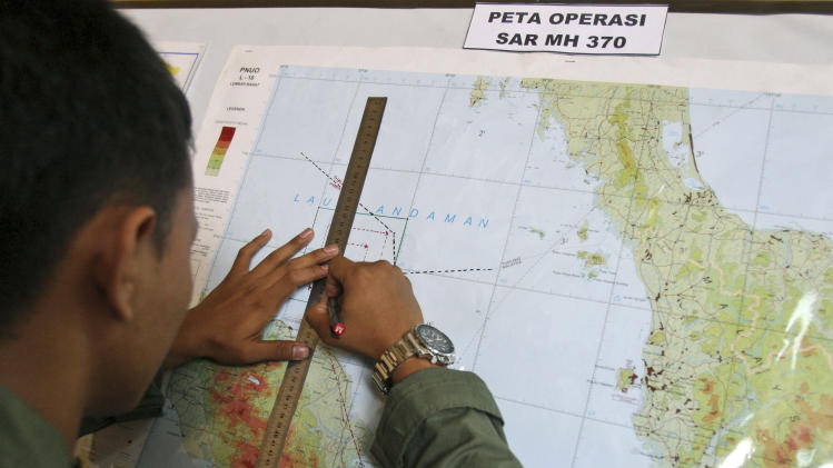 An Indonesian Air Force officer draws a flight pattern flown earlier in a search operation for the missing Malaysia Airlines Boeing 777, during a post-mission briefing at Suwondo air base in Medan, North Sumatra, Indonesia, Thursday, March 13, 2014. The hunt for the missing jetliner has been punctuated by false leads since it disappeared with 239 people aboard about an hour after leaving Kuala Lumpur for Beijing early Saturday. (AP Photo/Binsar Bakkara)