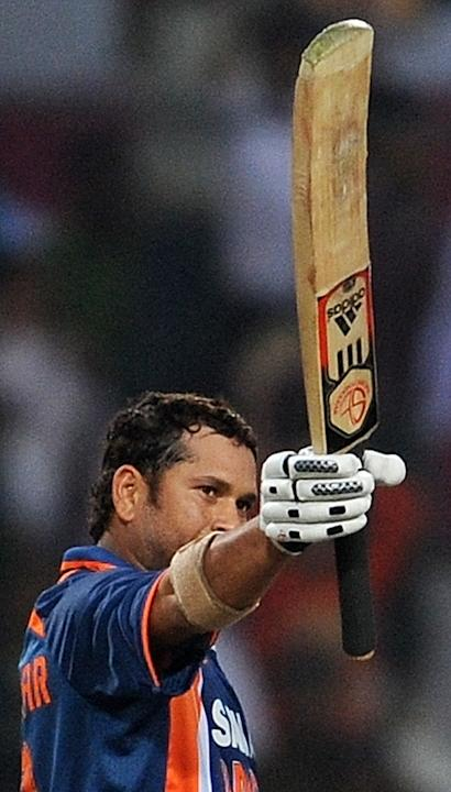 (FILES) This February 24, 2010 file photograph shows Indian cricketer Sachin Tendulkar as he raises his bat to celebrate scoring a world record breaking double century (200 runs) during the second One