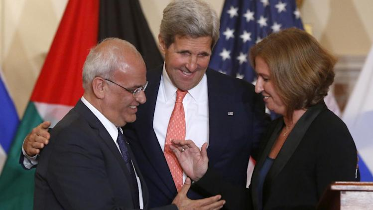 Secretary of State John Kerry stands between Israel's Justice Minister and chief negotiator Tzipi Livni, right, and Palestinian chief negotiator Saeb Erekat, as they shake hands after the resumption of Israeli-Palestinian peace talks, Tuesday, July 30, 2013, at the State Department in Washington. (AP Photo/Charles Dharapak)