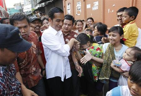 Jakarta's Governor Joko Widodo is greeted by residents during his visit to inspect the aftermath of a slum fire area in west Jakarta