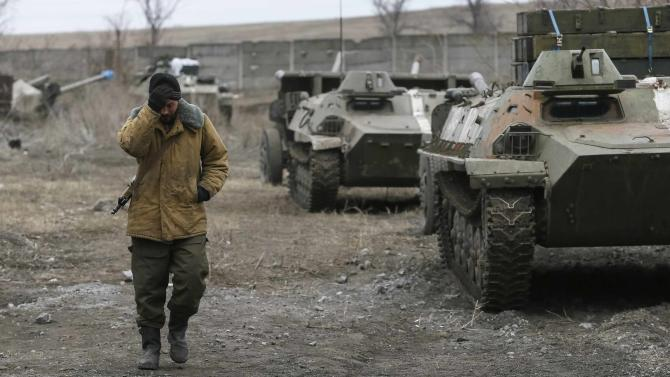 A Ukrainian serviceman walks past armoured personnel carriers, military vehicles and cannons at their new position as they pull back from the Horlivka region, near Druzhkivk
