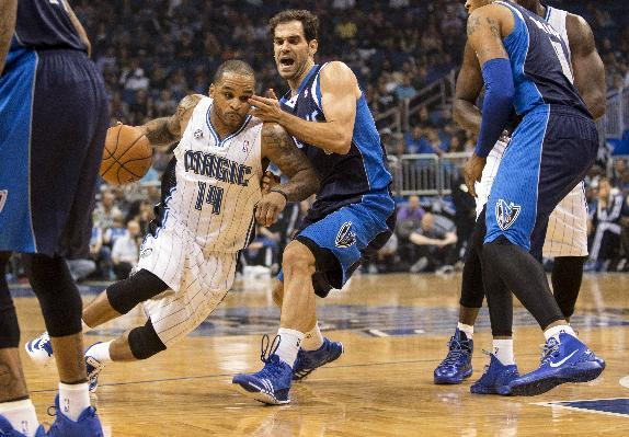Orlando Magic's Jameer Nelson, left, drives past Dallas Mavericks' Jose Calderon, center, during the first half of an NBA basketball game in Orlando, Fla., Saturday, Nov. 16, 2013