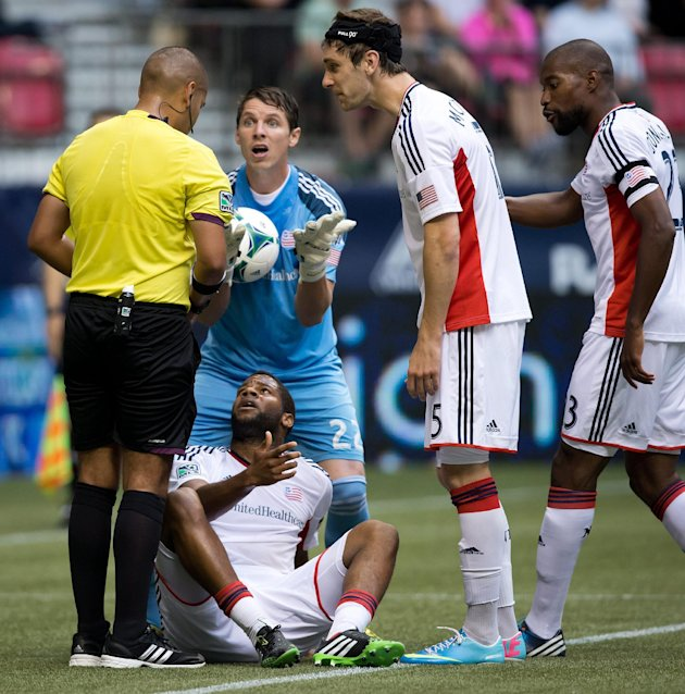 New England Revolution goalkeeper Bobby Shuttleworth, clockwise from center, Darrius Barnes, Jose Goncalves, of Portugal, and Andrew Farrell, bottom, protest to referee Juan Guzman after Farrell recei