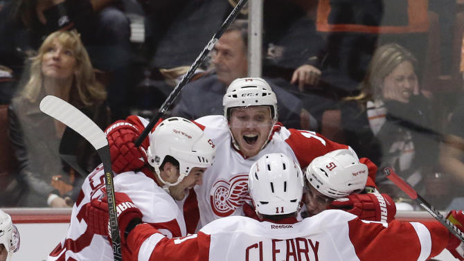 Detroit Red Wings center Gustav Nyquist, top, celebates his winning goal with Jonathan Ericsson, left, Daniel Cleary (11) and Valtteri Filppula against the Anaheim Ducks during overtime in Game 2 of their first-round NHL hockey Stanley Cup playoff series in Anaheim, Calif., Thursday, May 2, 2013. The Red Wings won 5-4. (AP Photo/Chris Carlson)