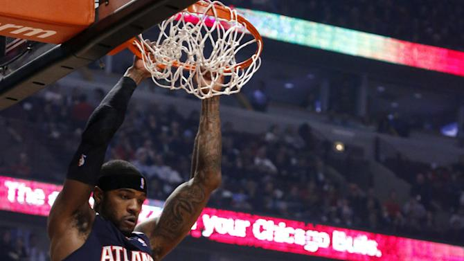 Atlanta Hawks forward Josh Smith (5) dunks in front of Chicago Bulls forward Carlos Boozer during the first half of an NBA basketball game Monday, Jan. 14, 2013, in Chicago. (AP Photo/Charles Rex Arbogast)