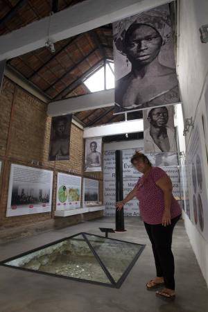 """In this Sept. 11, 2012 photo, Ana de la Merced Guimaraes points to remains of African slaves covered with a glass pyramid at her home in Rio de Janeiro, Brazil. In 1996, Merced Guimaraes and her husband Petrucio bought a fixer-upper in the historic port-side neighborhood of Gamboa. Once they started digging into the foundation, they made a startling discovery: the building sat atop the """"cemetery of new blacks,"""" - the burial place of newly arrived Africans who died soon after their arrival in Brazil between 1769 and 1830. (AP Photo/Silvia Izquierdo)"""