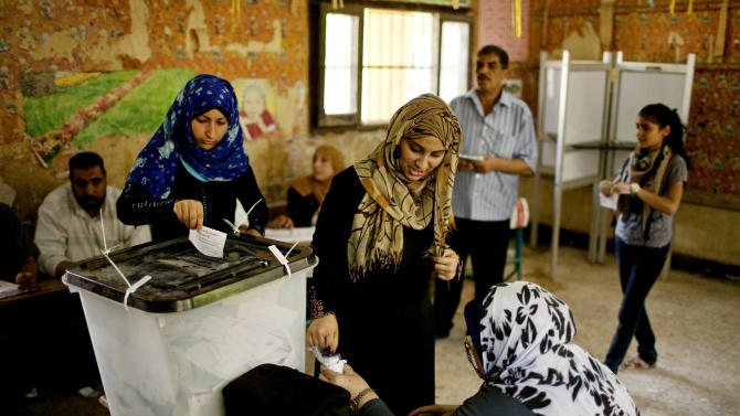 Egyptian women vote at a polling station in Shubrah El-Kheima, a working class, industrial area on the outskirts of Cairo, Egypt on Saturday, June 16, 2012. Egyptians voted Saturday in the country's landmark presidential runoff, choosing between Hosni Mubarak's ex-prime minister and an Islamist candidate from the Muslim Brotherhood after a race that has deeply polarized the nation. The two-day balloting will produce Egypt's first president since a popular uprising last year ousted Mubarak, who is now serving a life sentence.  (AP Photo/Pete Muller)