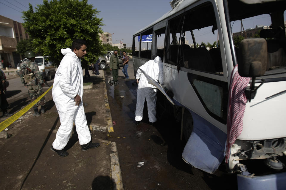 Forensic experts inspect the site of a damaged bus following a bomb attack in Sanaa, Yemen, Sunday, Aug. 25, 2013. A powerful blast ripped through the bus carrying air force personnel down a main street in Yemen's capital on Sunday, causing at least a score of casualties, officials said. (AP Photo/Hani Mohammed)