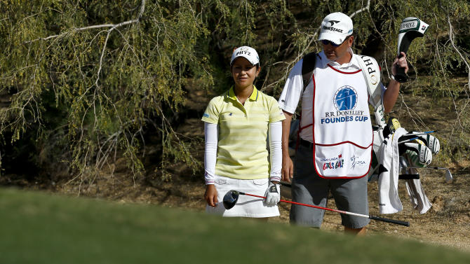 Ai Miyazato, left, of Japan, and her caddie Michael Seaborn try to figure out what to do as he golfball sits in the desert rough on the 16th hole during the final round of the LPGA Founders Cup golf tournament on Sunday, March 17, 2013, in Phoenix. (AP Photo/Ross D. Franklin)