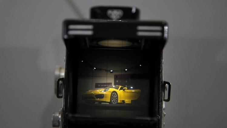 The new Porsche Cayman is seen through the viewfinder of a vintage TLR camera at the LA Auto Show in Los Angeles, Thursday, Nov. 29, 2012. (AP Photo/Jae C. Hong)