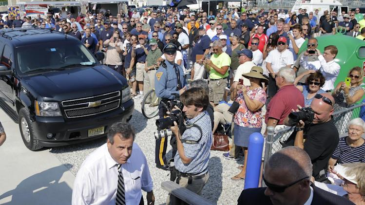 New Jersey Gov. Chris Christie, left, walks past a huge crowd of retired and active duty firefighters and police officers as he arrives at an event where he addressed a gathering about pension costs and other problems facing the state Tuesday, July 22, 2014, in Long Beach Township, N.J. (AP Photo/Mel Evans)