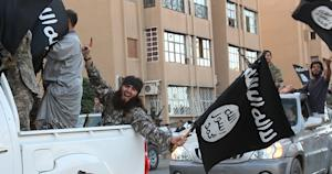 members of the Islamic State group parading in a street …