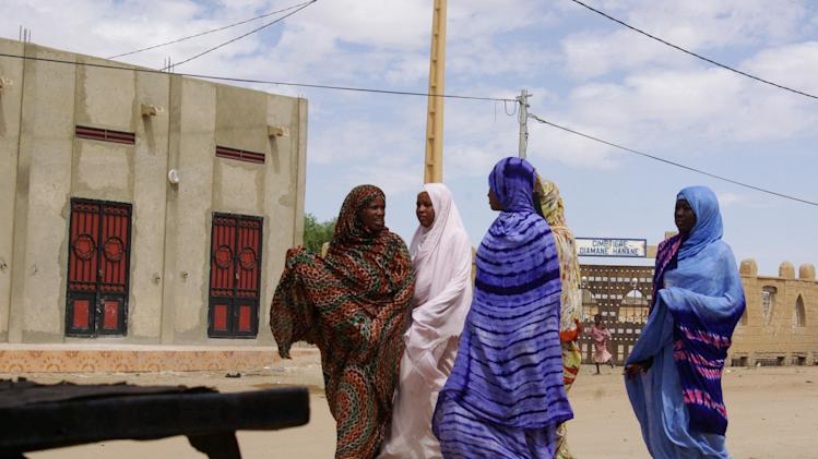 In this Oct. 18, 2012 photo, women wearing veils as mandated by Islamist group Ansar Dine, walk along a street in Timbuktu, Mali. In recent months, al-Qaida and its allies have taken advantage of political instability within Mali to push out of their hiding place and into the towns, taking over an enormous territory which they are using to stock arms, train forces and prepare for global jihad. And as 2012 draws to a close and the world hesitates, delaying a military intervention, the extremists who seized control of the area earlier this year are preparing for a war they boast will be worse than the decade-old struggle in Afghanistan. (AP Photo)