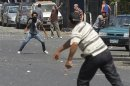 Local resident throws stones towards supporters of ousted President Mohamed Mursi during clashes in central Cairo