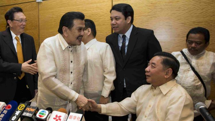 Manila Mayor Estrada shakes hand with Manila City Council member Ang after a news conference in Hong Kong