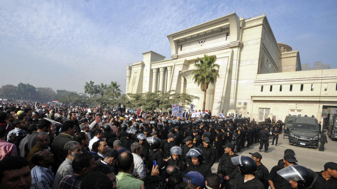Riot police form a cordon as several thousand supporters of Islamist President Mohammed Morsi surround the Supreme Constitutional Court on Sunday to prevent the judges from entering and ruling on the legitimacy of the nation's Islamist-dominated constituent assembly, Sunday, Dec. 2, 2012. A ruling from the court was postponed — but regardless of which way it goes — would be a direct challenge to Morsi, who last month gave himself near absolute powers, placing himself and the assembly above any oversight, including by the judiciary. (AP Photo/Ahmad Hammad)