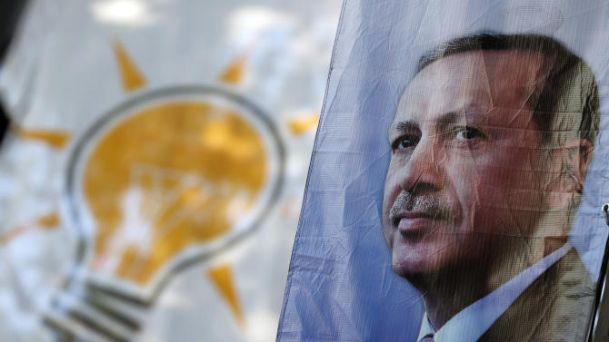 A poster of Turkey's President Recep Tayyip Erdogan, is seen backdropped by a banner for the upcoming elections with the symbol of his AKP party, in Istanbul, Turkey, Tuesday, May 26, 2015. Turkey will hold general election on June 7, 2015. All eyes will be on the pro-Kurdish People's Democratic Party (HDP)HDP. If it reaches the minimum 10 percent threshold required for entering parliament as a party, it could effectively thwart Erdogan's ambition to lead a presidential system following a constitutional change. (AP Photo/Emrah Gurel)