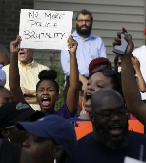 Demonstrators peacefully gather Thursday, Aug. 14, 2014, at the site where Michael Brown was shot and killed by police in Ferguson, Mo. The Missouri Highway Patrol seized control of a St. Louis suburb Thursday, stripping local police of their law-enforcement authority after four days of clashes between officers in riot gear and furious crowds protesting the death of an unarmed black teen shot by an officer. (AP Photo/Jeff Roberson)