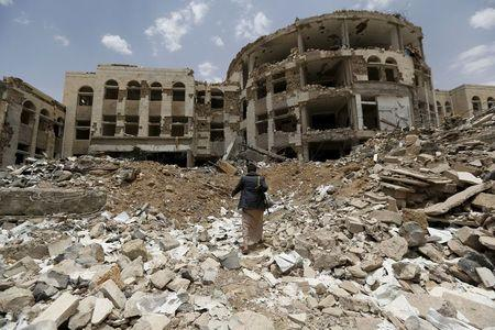 Houthi militant walks in front of a government compound, destroyed by recent Saudi-led air strikes, in Yemen's northwestern city of Amran