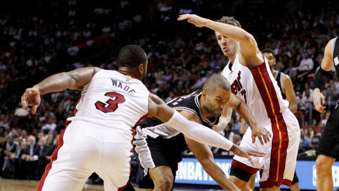 San Antonio Spurs guard Tony Parker, center, drives between Miami Heat defenders Dwyane Wade and Goran Dragic in the first half of an NBA basketball game, Tuesday, March 31, 2015, in Miami. The Spurs won the game 95-81. (AP Photo/Joe Skipper)