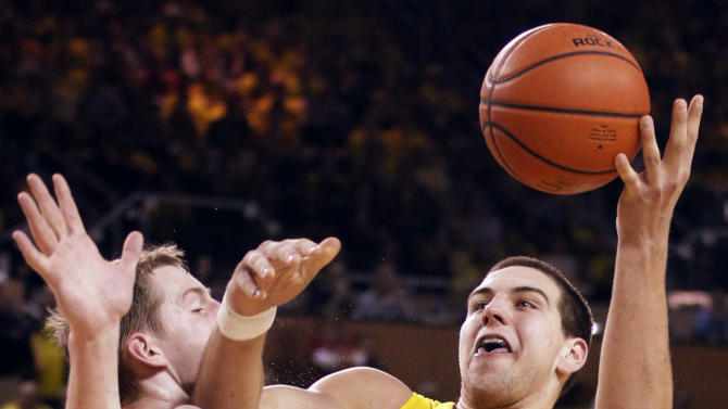 Michigan forward Mitch McGary (4) tries going to the basket against Indiana forward Cody Zeller (40) during the second half of an NCAA college basketball game Sunday March 10, 2013, in Ann Arbor, Mich. Indiana defeated Michigan 72-71 to win the Big Ten title. (AP Photo/Duane Burleson)