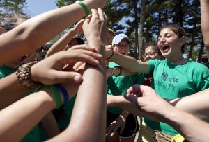 Campers cheer before taking the field for a softball …