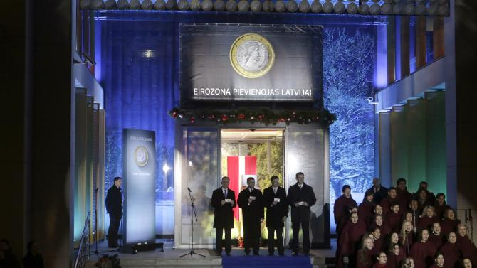 Latvia's central bank governor Ilmars Rimsevics, Estonia's Prime Minister Andrus Ansip, Latvia's Prime Minister Valdis Dombrovskis and Latvia's Minister of Finance Andris Vilks, pose with euro banknotes during an official event in Riga