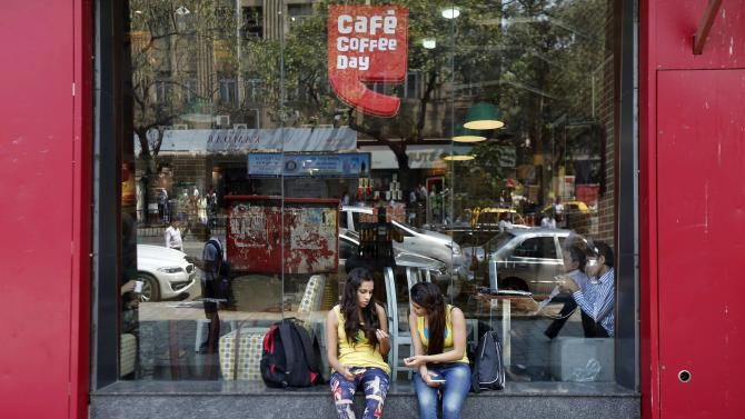 Girls sit at the window of a Cafe Coffee Day outlet in Mumbai