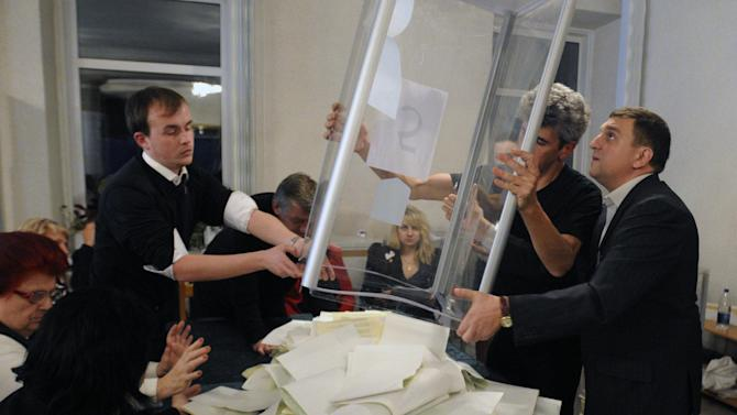 Members of a local election commission open a ballot box to count votes after a day of election at a polling station in Kiev, Ukraine, Sunday, Oct. 28, 2012. Ukrainians are electing a parliament on Sunday in a crucial vote tainted by the jailing of top opposition leader Yulia Tymoshenko and fears of election fraud.  (AP Photo/Sergei Chuzavkov)