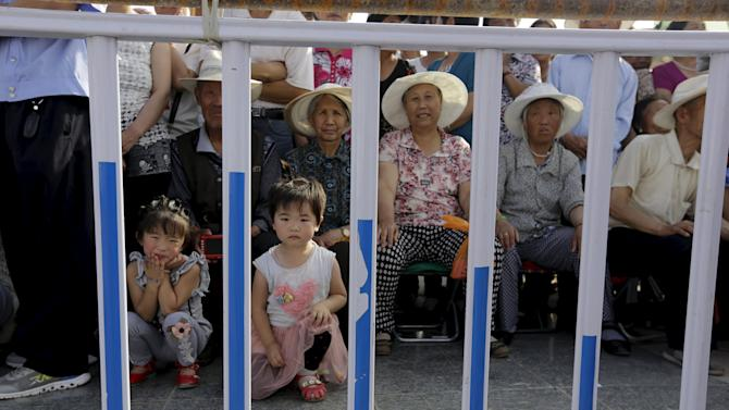 Local villagers sit outside the fence as they wait for IOC's announcement of the winner city for the 2022 winter Olympics bid in Chongli county of Zhangjiakou