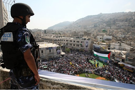 A Palestinian police officer watches a rally in support of the Palestinian bid for statehood recognition in the United Nations, in the West Bank city of Nablus, Wednesday, Sept. 21, 2011. Thousands of flag-waving Palestinians rallied Wednesday in towns across the West Bank to show support for their president's bid to win U.N. recognition of a Palestinian state.  (AP Photo/Nasser Ishtayeh)