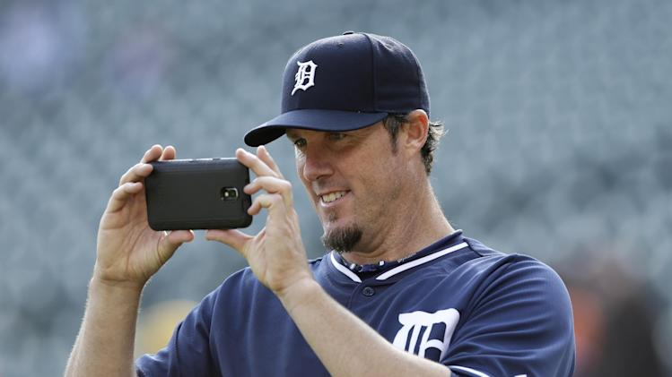 Detroit Tigers relief pitcher Joe Nathan photographs his son with Tigers' guests during batting practice before a baseball game against the Los Angeles Angels in Detroit, Friday, April 18, 2014. (AP Photo/Carlos Osorio)