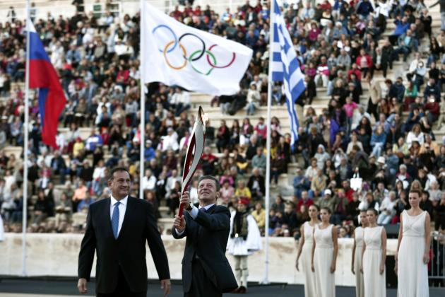 Russia's Deputy Prime Minister Kozak raises an Olympic torch for the Sochi 2014 Winter Games next to President of the Greek Olympic Committee Kapralos during a handover ceremony in Athens