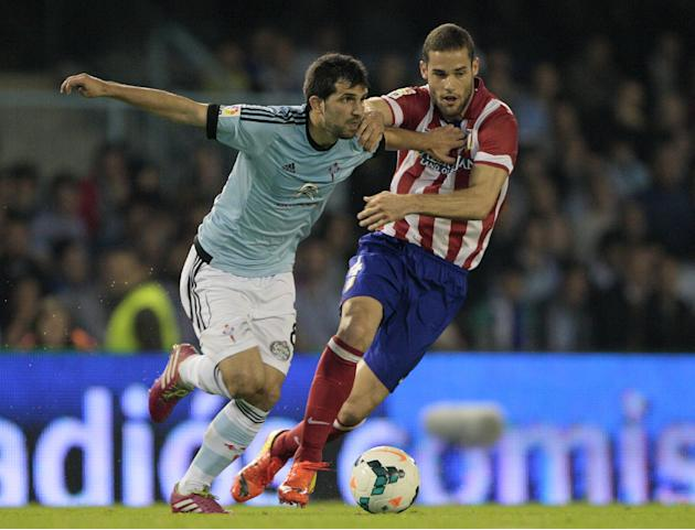 Real Club Celta's Alex Lopez, left, in action with Atletico's Mario Suarez during a Spanish La Liga soccer match at the Balaidos stadium in Vigo, Spain, Saturday, March 8, 2014