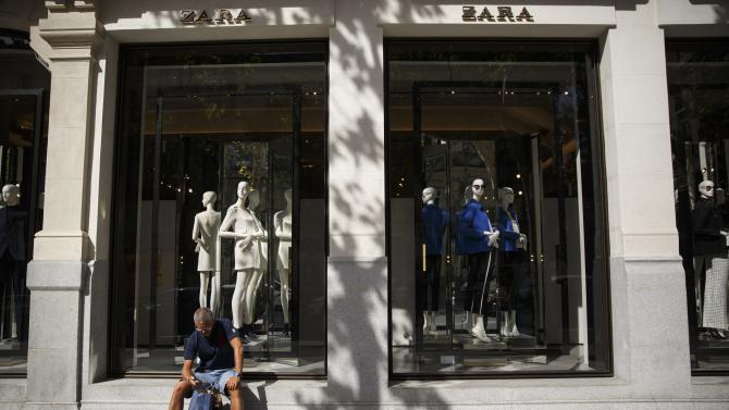 A man sits outside a Zara store in Madrid