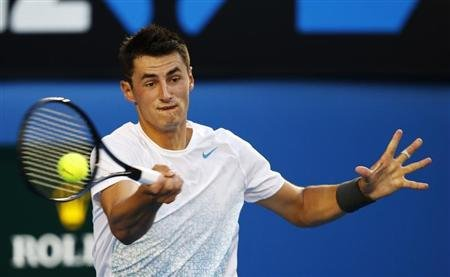 Bernard Tomic of Australia hits a return to Roger Federer of Switzerland during their men's singles match at the Australian Open tennis tournament in Melbourne