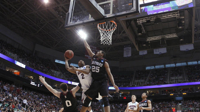 Arizona's Mark Lyons shoots between Harvard's Kenyatta Smith, right, and Laurent Rivard, left, in the second half during a third-round game in the NCAA men's college basketball tournament in Salt Lake City on Saturday, March 23, 2013. Arizona defeated Harvard 74-51. (AP Photo/George Frey)