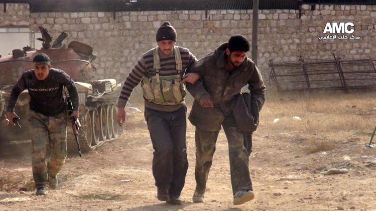 This Monday, Nov. 11, 2013 citizen journalism image provided by Aleppo Media Center AMC which has been authenticated based on its contents and other AP reporting, shows two Free Syrian Army fighters helping a wounded comrade during clashes in Aleppo, Syria. Activists say clashes have flared up between Syrian troops and rebels on the southern outskirts of Damascus as part of a weeks-long government push to advance on opposition-held areas. (AP Photo/Aleppo Media Center AMC)