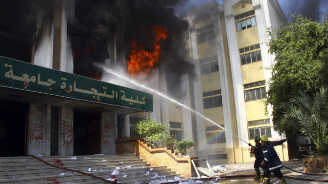 Firemen put out a fire inside the Faculty of Commerce, that was started after a student was killed under disputed circumstances during clashes, at al-Azhar University, in the Nasr City suburb of Cairo, Egypt, Saturday, Dec. 28, 2013. Al-Azhar students have been protesting for weeks against the ouster of Islamist President Mohammed Morsi who hails from the Muslim Brotherhood-- a group that Egyptian authorities designated a terrorist organization. (AP Photo/Ahmed Ramadan)