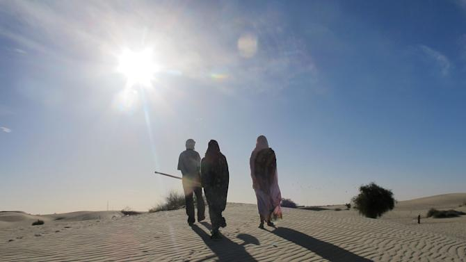 Ani Boka Arby, center, and her family walk back through the desert in Timbuktu, Mali Friday Feb. 8, 2013 after discovering the site where the body of Arby's husband, Mohamed Lamine, was dumped. Ahead of her is her father who used a shovel to unearth his corpse.  Lamine, an Arab, was last seen being led away at gunpoint by Malian soldiers on Jan. 28. Children found his body and that of another Arab man days later, lying facedown in the side of a dune on the outskirts of this desert capital. Human rights groups have warned that the military intervention to take back the territory in Mali's north which was occupied by al-Qaida-linked extremists last year, could open the door to reprisals killings. Especially vulnerable are ethnic minorities suspected of having supported the extremists, including the country's Arabs. (AP Photo/Rukmini Callimachi)