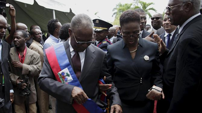 Provisional Haitian President Jocelerme Privert adjusts the presidential sash as he walks with his wife Ginette in the gardens of the National Palace during his inauguration in Port-au-Prince