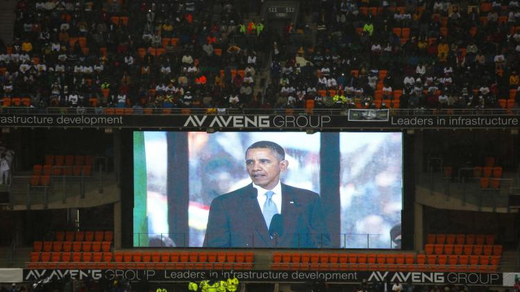 Mourners watch U.S. President Barack Obama addressing the crowd during the national memorial service for late former South African President Nelson Mandela in Johannesburg's National Bank Stadium