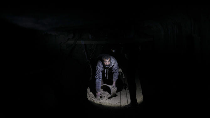 A Palestinian cleans a tunnel in Rafah, on the border between Egypt and the southern Gaza Strip, Thursday, Feb. 19, 2013 . The Gaza Strip's Hamas government and local smugglers accused Egypt Tuesday of flooding cross-border tunnels with sewage water in order to halt a thriving smuggling trade that has helped prop the local economy for more than five years. (AP Photo/Hatem Moussa)