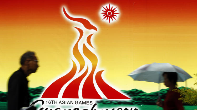 Two people walk past an Asian Games sign in Guangzhou, China, Wednesday, Nov. 10, 2010, ahead of  the Asian Games.(AP Photo/Rob Griffith)
