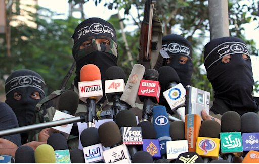 Masked Palestinian militants from the Popular Resistance Committees speak during a news conference in Gaza City, Monday, Aug. 22, 2011. Palestinian militants in the Hamas-ruled Gaza Strip fired rockets and mortars into southern Israel early Monday, despite an unofficial truce meant to defuse days of escalating violence. Around midday, The Popular Resistance Committees, a group that had held out from joining the cease-fire, announced it would comply. (AP Photo/Hatem Moussa)
