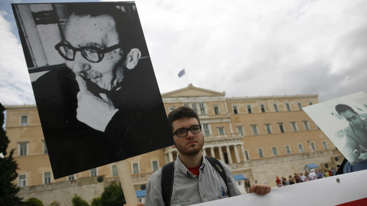 """A protester holding a placard with the image of Greek writer and philosopher Nikos Kazantzakis, writer of the novel """"Zorba the Greek"""", takes part in a protest in front of the Parliament in Athens, Friday, June 14, 2013. Workers at the Hellenic Broadcasting Corp. or ERT have continued to occupy the broadcaster's headquarters and maintain online and satellite broadcasts since the government shut down the station Tuesday, citing the need to make austerity cuts and promising to relaunch with fewer staff before the end of the summer. (AP Photo/Kostas Tsironis)"""