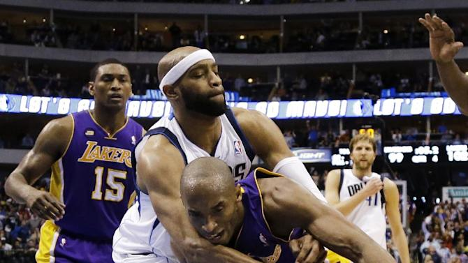 Dallas Mavericks' Vince Carter, center, fouls Los Angeles Lakers' Kobe Bryant as the two chase down a loose ball late in the second half of an NBA basketball game, Sunday, Feb. 24, 2013, in Dallas. The Lakers won 103-99. (AP Photo/Tony Gutierrez)
