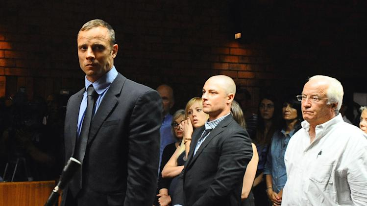 "FILE - In this photo taken Tuesday, Feb. 19, 2013 Olympian Oscar Pistorius stands following his bail hearing, as his brother Carl, center, and father Henke look on, in Pretoria, South Africa. The family of Oscar Pistorius, the double-amputee Olympian charged with murdering his girlfriend, is feuding publicly about whether guns are a necessary protection against crime in South Africa. British newspapers quoted Pistorius' father, Henke Pistorius, as saying the family owned handguns for self-defense and suggesting that South Africa's government shares blame for ""white crime levels"" in the country. In a statement Tuesday March 5, 2013 quoting the runner's uncle, Arnold Pistorius, the family subsequently distanced itself from the father's comments. (AP Photo/Masi Losi/Pretoria News) SOUTH AFRICA OUT"