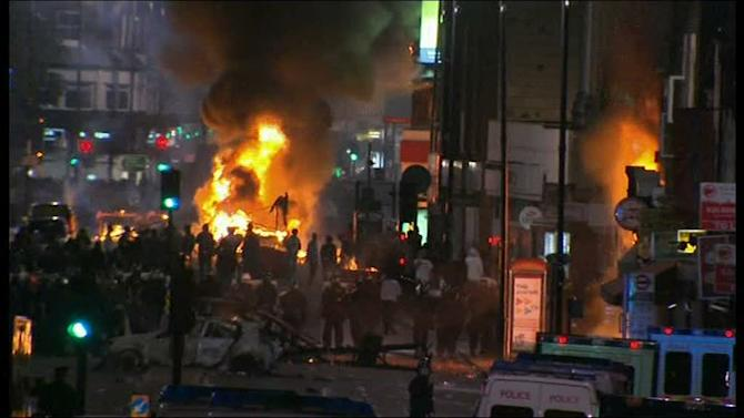 "In this image from video, a bus and shop burn in  Tottenham, north London late Saturday Aug 6 2011 after two police cars were attacked by members of a community where a young man was shot dead by police on Thursday, took to the streets to demand ""justice"".  Officers had been attempting to carry out an arrest under the Trident operational command unit, which deals with gun crime in the black community, according to the Independent Police Complaints Commission . (AP Photo/Sky tv via APTN ) UNITED KINGDOM OUT  NO SALES   TV OUT"